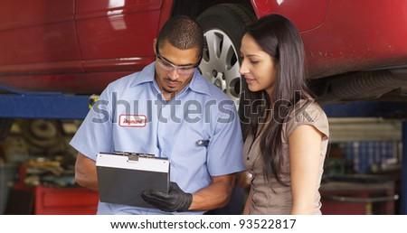 Auto shop mechanic works with customer - stock photo