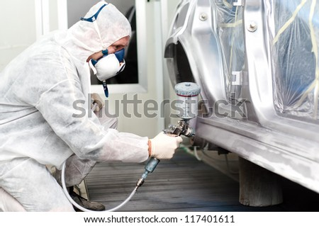 auto worker spraying grey paint on a car in an auto garage - stock photo