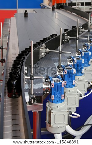 Automated conveyor belt with bottles at production line - stock photo