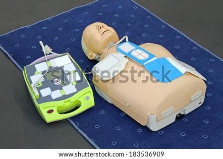 Automated External Defibrillator with training dummy mannequin - stock photo