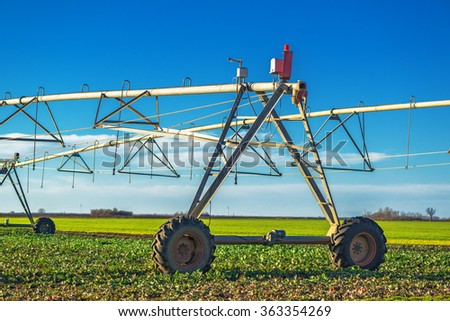 Automated farming irrigation sprinklers on cultivated field - stock photo