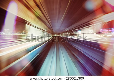 Automated guide-way train at night through the city lights - stock photo