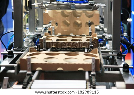 Automated line for manufacturing of cardboard boxes for sour cream - stock photo