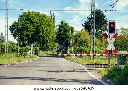 Automated rural level crossing with the barriers down and flashing red light