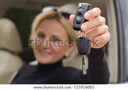 Automatic car key holding by the woman inside the car