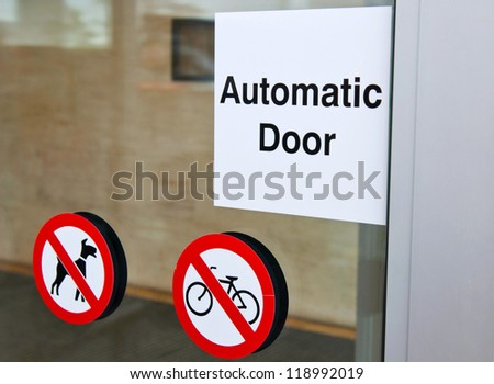 automatic door sign on shopping mall entrance (dogs and bicycles are forbidden) - stock photo
