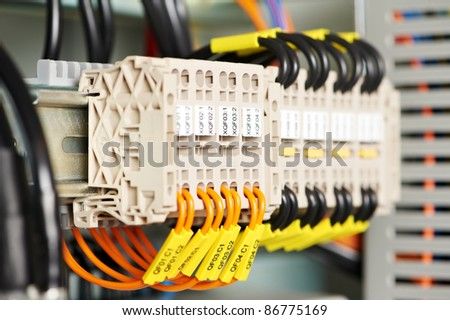 Automatic electrical fuseboxes and power lines located inside of an industrial switch control panel board - stock photo