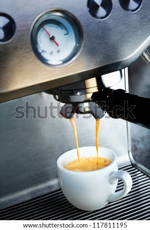 Automatic filter coffee machine dispensing a cup of delicious hot frothy aromatic coffee into a white ceramic cup in a catering and hospitality background