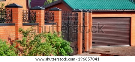 Automatic Garage rolling Gate and brick fence - stock photo