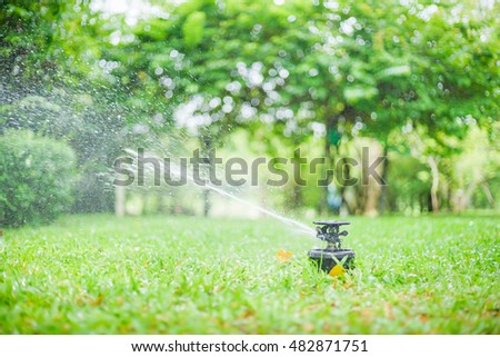 Automatic Garden Lawn sprinkler in action watering grass. Green Nature Background concept
