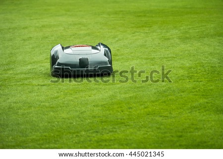Automatic lawn mower robot mowing grass in garden, front view, selective focus