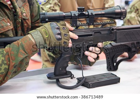 Automatic rifle and a man in camouflage uniform. Weapon - stock photo