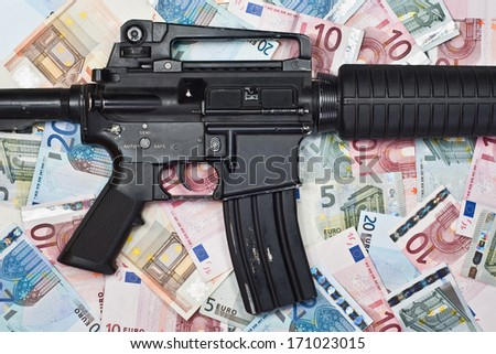 automatic rifle on a background of euro banknotes - stock photo