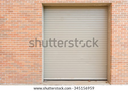 automatic roll up steel warehouse door on brick wall - stock photo
