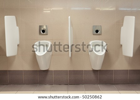 Automatic urinals in a modern toilet - stock photo