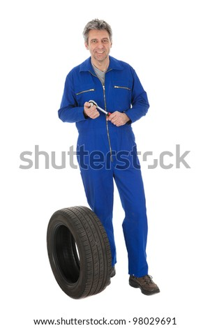 Automechanic standing next to car tire. Isolated on white