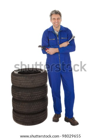 Automechanic standing next to car tires. Isolated on white - stock photo
