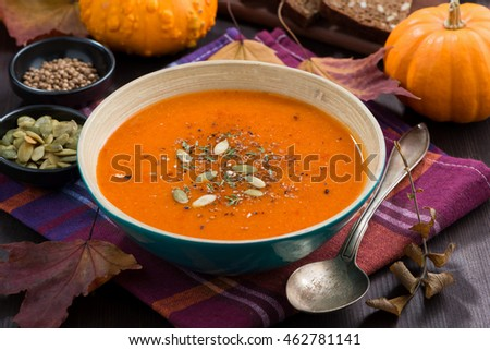 automn pumpkin soup in a bowl on table, horizontal