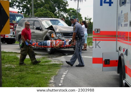 Automobile accident, July 3, 2006 12:50 pm on Immokalee Florida. Victim on stretcher. Car involved is in background. - stock photo