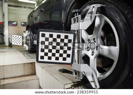 Automobile car wheels with computerized alignment machine clamp - stock photo