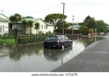 Automobile caught in storm-water drain overflow - stock photo