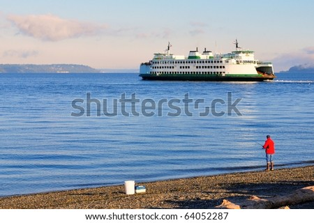 Automobile ferry crossing water with fisherman in the foreground - stock photo