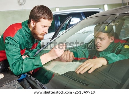Automobile glazier repairman teaching or discussing with partner windscreen repair of a car in auto service station garage - stock photo