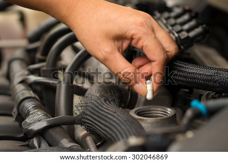 Automobile, grandmother, maintenance, Mechanic pouring concentrated oil into car at the repair garage.