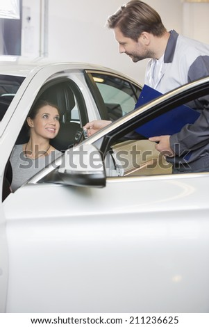 Automobile mechanic giving car key to female customer in repair shop - stock photo