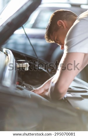Automobile mechanic repairing a car in service station - stock photo