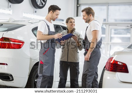 Automobile mechanics discussing over clipboard in car repair shop - stock photo