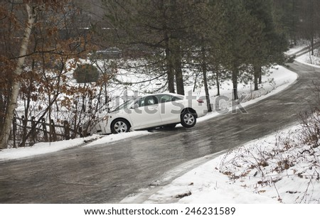 automobile on icy winding country road - stock photo