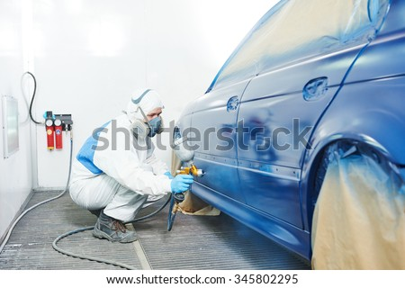 automobile repairman painter in protective workwear and respirator painting car body bumper in paint chamber - stock photo