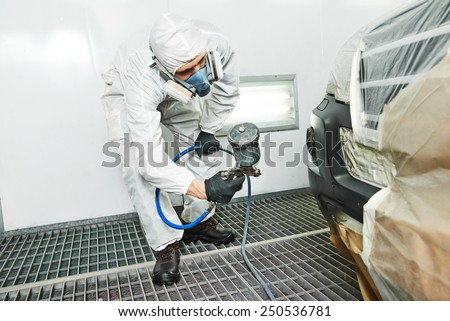 automobile repairman painter painting car body bumper in chamber - stock photo