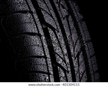 Automobile wet tyre on a black background - stock photo