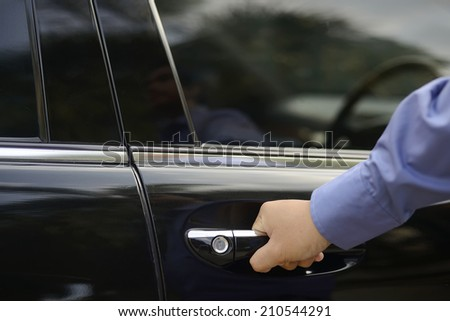 Automotive and transportation concept. Man hand on door handle of car - stock photo