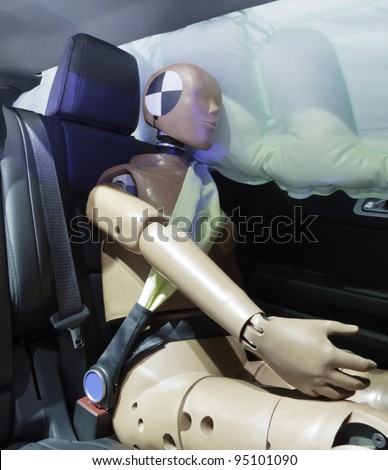 Automotive crash test dummy strapped into car seat, head against air bag