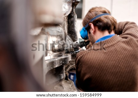 Automotive engineer working on the bodywork of a car, grinding the metal surfaces with professional tools - stock photo