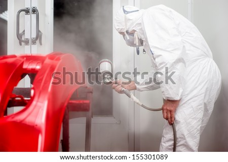 Automotive industry - worker painting and working on the body of a car - stock photo
