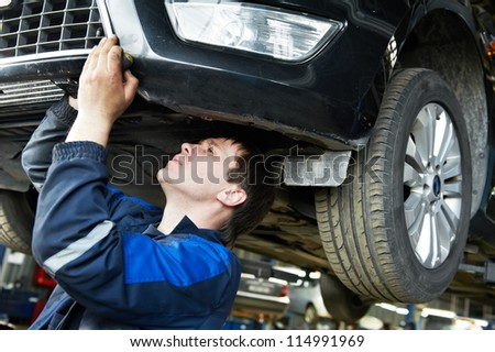 automotive mechanic worker examining car bottom during automobile car maintenance at lever repair service station - stock photo