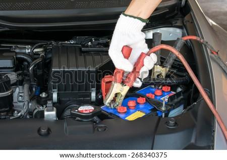 automotive technician charging vehicle battery - stock photo