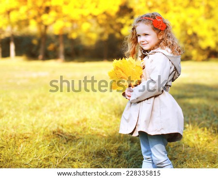 Autumn and people concept - beautiful little girl with yellow maple leafs in the park outdoors - stock photo