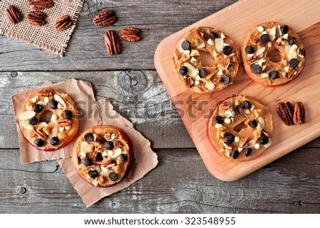 Autumn apple rounds with peanut butter, chocolate chips and nuts, downward view on rustic wood - stock photo