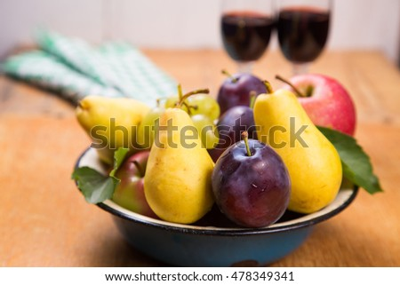 autumn apples,blue plums,peach and grape with red wine in dish