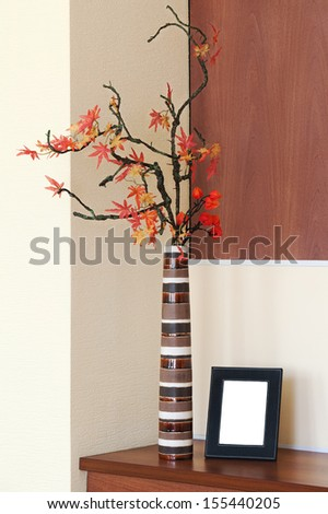 Autumn arrangement in a vase on the table and photoframe with place for your foto. - stock photo