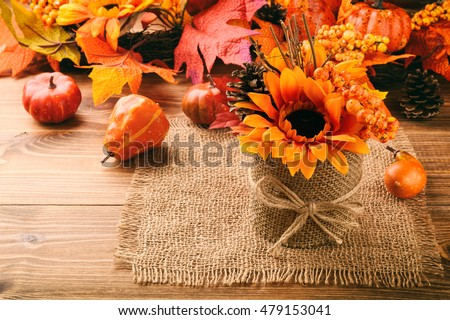 Autumn arrangement - pot with artificial sunflower  and leaves on wooden background.