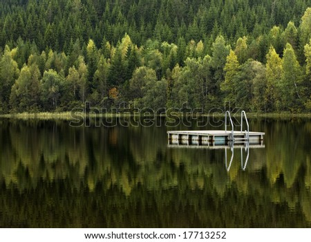 Autumn at a Swedish lake with reflection ,and where the  raft is waiting for the next season - stock photo