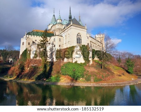 Autumn at famous Bojnice castle and a moat as viewed from the south side. Bojnice castle is the best known Slovak castle and it is very popular for tourists because of romantic nature of this place.