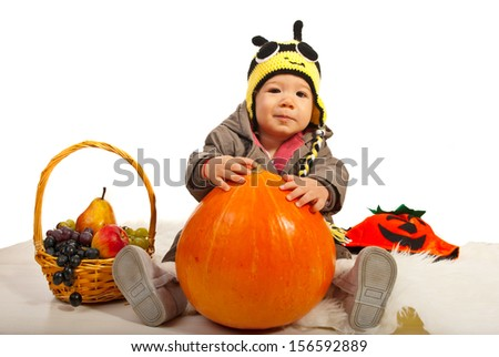 Autumn baby boy with bee hat holding big pumpkin against white background - stock photo