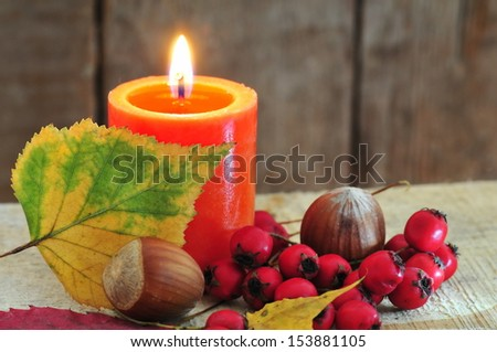 Autumn background with candle and yellow leaves - stock photo